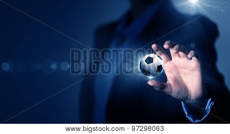 Close up of elegant businessman holding soccer ball in hand
