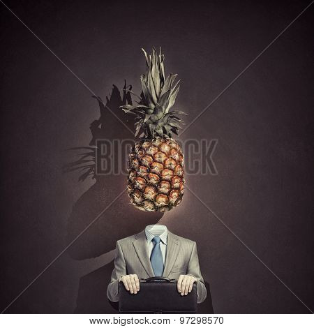 Headless businessman with pineapple instead of head