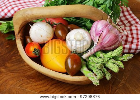 asparagus, tomatoes, garlic, mushrooms in a basket on a wooden background