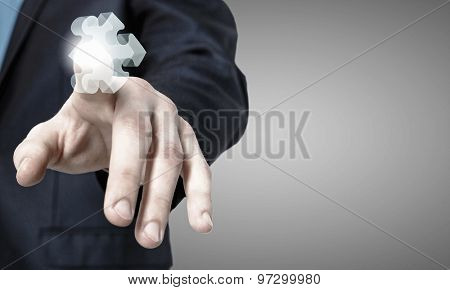 Close up of businessman's hand touching abstract puzzle piece