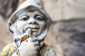 image of gnome  - Macro view of antique garden gnome against concrete brick wall shallow DOF - JPG