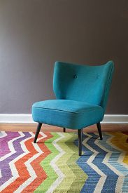 stock photo of chevron  - Single teal blue armchair and colorful chevron pattern rug interior grey wall - JPG