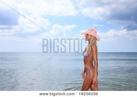 Sexy and fit blond woman wearing a pink hat  in the sea
