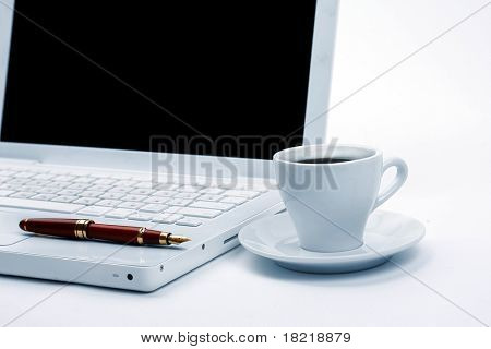 Cup of hot black steaming coffee on a laptop computer