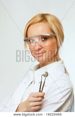 Image of assistant in sterile mask holding dentistry tools in hands