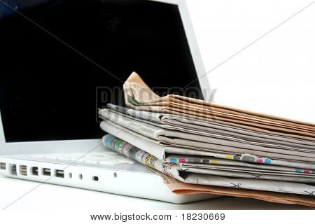 stack of newspaper next to a laptop