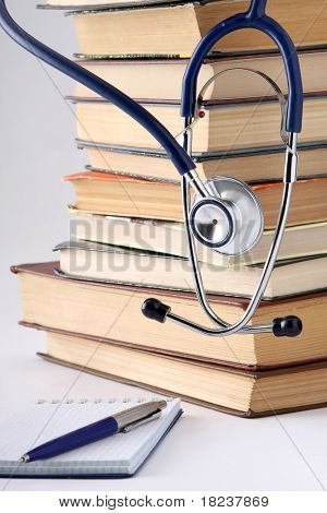 a stethoscope on a pile of books and a notebook with a pen