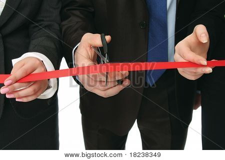 Business people cutting a red ribbon with a pair of scissors, closeup