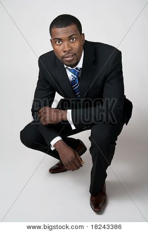 Business Man In Black Suit Squatting
