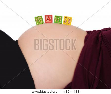 alphabet blocks resting on pregnant belly