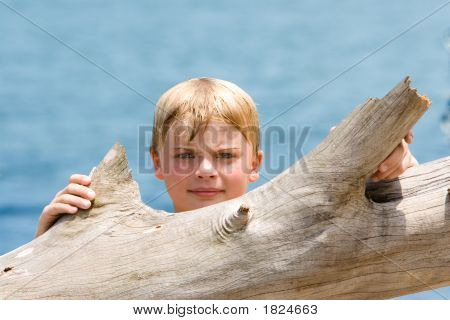 Boy Looking Over Driftwood