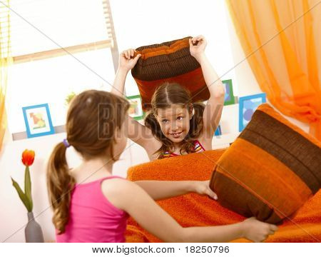 Happy schoolgirls in pillow fight in living room.?