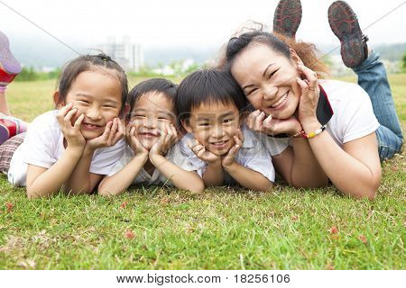 Happy mother's day. asian mother and her children on the green field