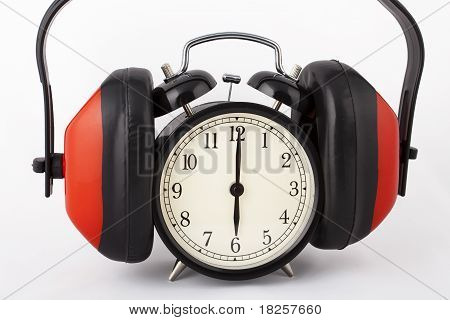 Alarm clock with ear defenders on.