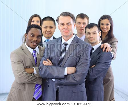 Group of co-workers standing in office space smiling