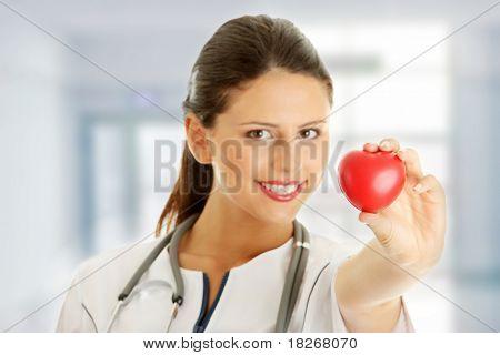 Junge Krankenschwester mit Herz in der Hand, isolated on white background