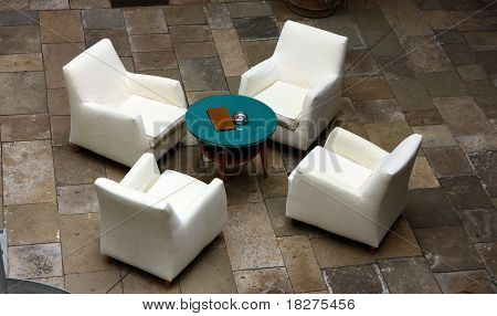 four white luxury chairs and rounded table
