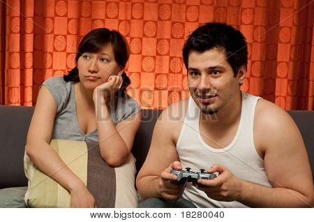 Young Couple Sitting On A Couch. The Guy Is Playing Vide Games, While The Girl Is Bored