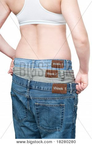 Yuong Woman Monitoring Weight Loss By Wearing Tree Jeans.