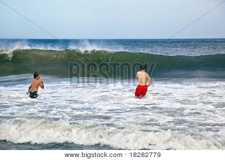 brothers enjoy walking in the beautiful ocean with waves