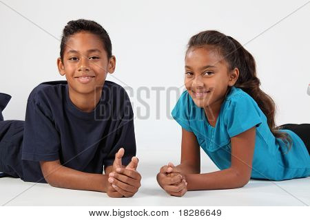 Happy school friends boy and girl sitting together