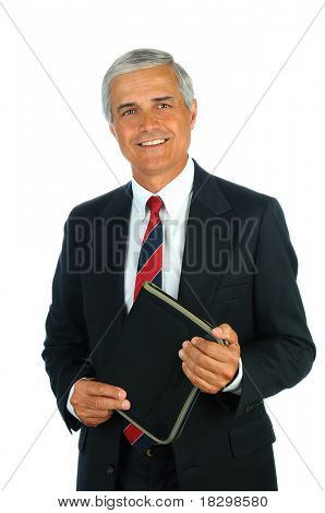 Portrait of a smiling middle aged business man holding a small binder with both hands. Vertical format isolated on white.