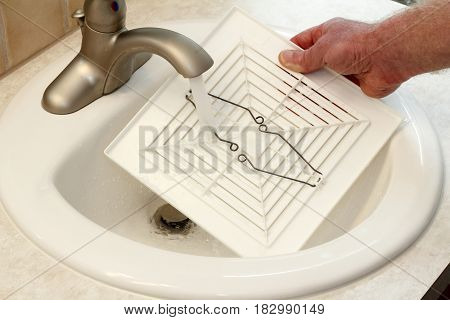 Male hand rinsing dust and dirt from inside of a ceiling fan cover with water from a bathroom sink faucet. Hand of a man washing a ceiling fan cover in a bathroom sink.