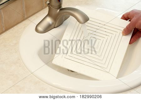 One white plastic grid front that covers a ceiling fan is being washed in a bathroom sink by the hand of a man. Front of a white ceiling fan cover being washed in a sink.