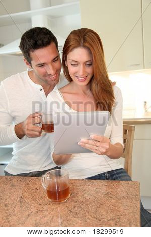 Young couple using electronic tablet in home kitchen