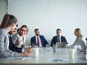 Group of cheerful business people smiling and chatting at meeting table in conference room poster