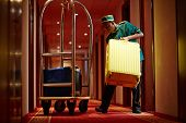 Hotel servant taking out suitcase with baggage from hotel room poster