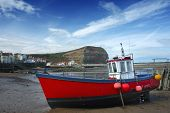stock photo of safe haven  - A small fishing boat in the harbour at Staithes  - JPG