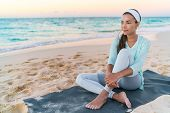 Yoga beach woman relaxing on fitness mat after workout. Fit Asian fitness athlete girl doing exercis poster