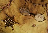 foto of bifocals  - Glasses and sea wheel on the old map - JPG