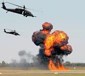 foto of attack helicopter  - Helicopters mounting a ground attack with explosions and smoke - JPG