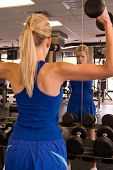 stock photo of workout-women  - Beautiful blond woman lifting weights while looking in a mirror in a fitness center - JPG