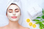 Spa Woman applying Facial clay Mask. Beauty Treatments. Close-up portrait of beautiful girl with a t poster