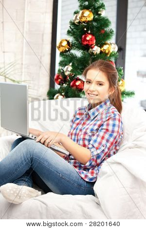picture of happy woman with laptop computer and christmas tree