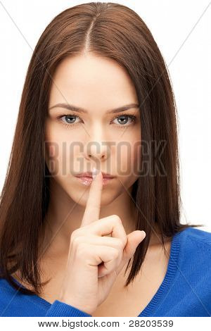 bright picture of young woman with finger on lips.