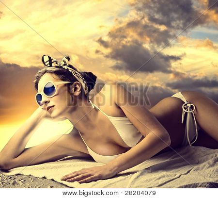 Beautiful woman lying on the sand and tanning