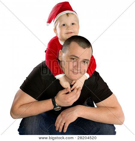 Adorable boy in festive santa uniform sitting on the back of his father