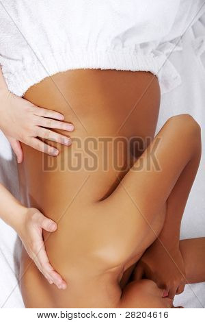 Pregnant woman being wrapped with a towel, lying on a bed and having a massage.