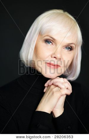 Portrait of mature blond female looking at camera on black background