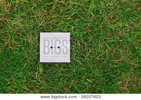 Green Energy Concept: Electric Outlet On A Grass