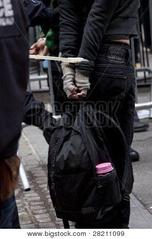 NEW YORK - NOV 17:  Police check the knapsack belonging to an unidentified woman arrested at Broad and Beaver Streets during the Occupy Wall Street protests on November 17, 2011 in New York City, NY.