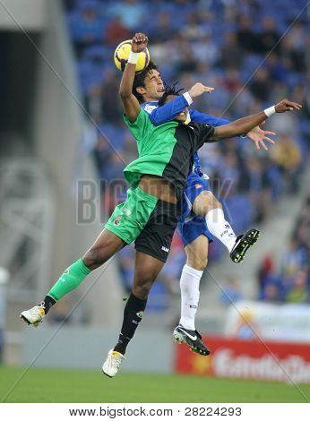 BARCELONA - DEC. 6: Tchite (L) of Santander  with Pillud (R) of Espanyol during a Spanish League match between Espanyol and Santander at the Estadi Cornella on December 6, 2009 in Barcelona, Spain