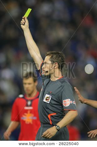BARCELONA, SPAIN - MAY 8: Referee Jose Luis Gonzalez delivers yellow card during Spanish soccer league match between Espanyol and Osasuna at the Estadi Cornella on May 8, 2010 in Barcelona, Spain