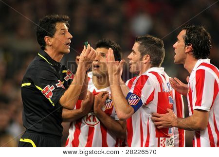 BARCELONA - FEB 5: Atletico Madrid players discuss with the referee Turienzo Alvarez during the match between FC Barcelona and Atletico at the Nou Camp Stadium on February 5, 2011 in Barcelona, Spain
