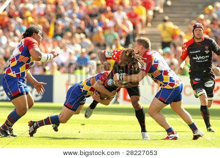 BARCELONA - APRIL 9: Toulons's Gabiriele Lovobalavu is tackled by Perpignan's players during the European Cup match USAP Perpignan vs RC Toulon at the Olympic Stadium on April 9, 2011in Barcelona, Spain