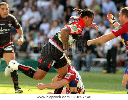 BARCELONA - APRIL 9: Toulons's Christian Loamanu is tackled by Perpignan's player during the European Cup match USAP Perpignan against RC Toulon at the Olympic Stadium in Barcelona, on April 9, 2011